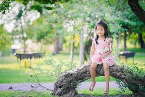 Asian girl with a doll sitting in the park