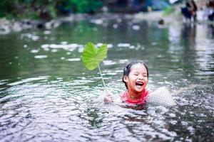 Little Asian girl playing in water with lotus leaf photo