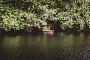 Red canoe on the river bank