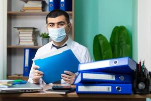Businessman holding a file with a mask on