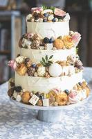 Traditional wedding cake decorated with fruits, biscuits, macaroon and flowers