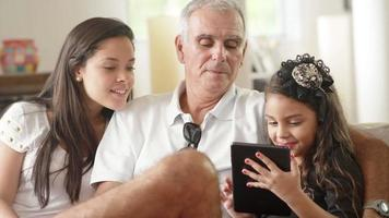 Grandfather using a tablet computer with grandchildren in living room video