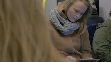 Young woman using tablet computer in subway train video