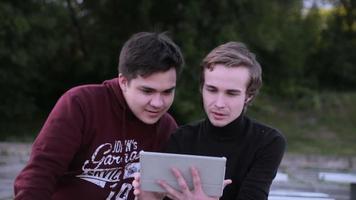 Deux amis masculins avec ordinateur tablette parler surf en plein air