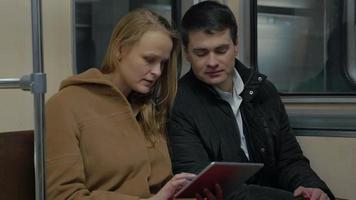 Young people using tablet computer in moving subway train video