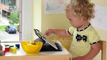 Baby girl using tablet computer. Toys and food laying on table video