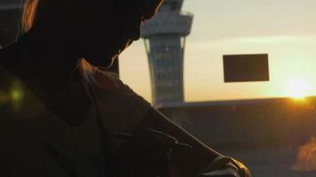 Frau mit intelligenter Uhr im Flughafen bei Sonnenuntergang