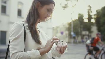 mulher usa smartwatch parado na cidade velha em câmera lenta