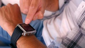 homme utilisant smart watch sur canapé video