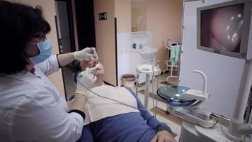 dentista che esamina la bocca di un paziente con una telecamera intraorale. video