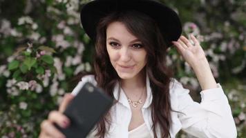 femme heureuse prenant selfie sur tablette dans le jardin fleuri. video
