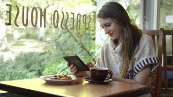 Une jeune femme est assise à une table dans un café et regarde sa tablette tout en buvant son cappuccino