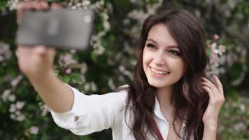 mujer feliz tomando selfie en tableta en el jardín floreciente. video