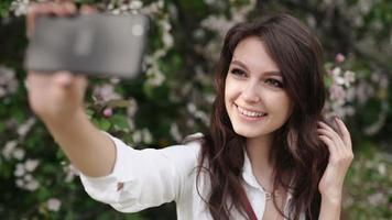 Happy woman taking selfie on tablet in the blooming garden.