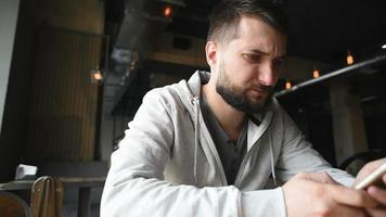 Portrait of young beard man with smartphone sitting in restaurant video