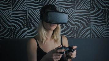 Virtual reality game. Girl with pleasure uses head-mounted display at home video
