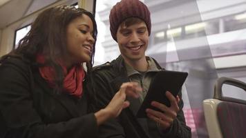 pareja joven en una cita use una tableta en un tren