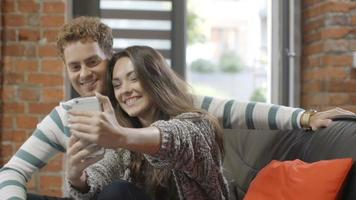 Happy young couple using smartphone at home. video