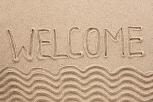Word welcome written on the sand photo