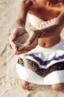 manos de mujer sosteniendo arena en la playa foto