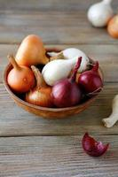 Onions and dried husk in clay bowl on wooden boards photo