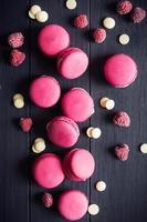 Raspberry macaroons on black wooden background