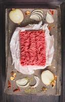 Carne molida cruda sobre mesa de madera con especias y cebolla foto