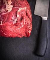 Filete de ternera cruda sobre mesa de pizarra con cuchillo foto