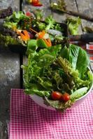 Preparación de ensalada de verduras sobre fondo de tablero de madera