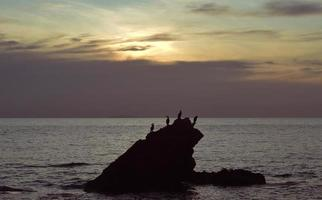 Silhouette of small island in the ocean photo