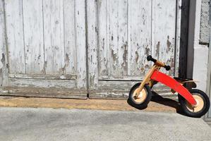 Toddler's orange bicycle park beside door