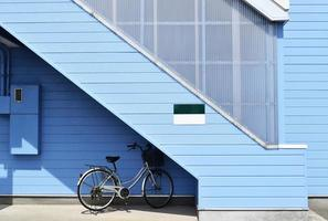 Gray bike parked near blue house photo