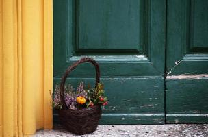 Brown basket filled with flower near colorful doorstep