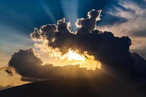 golden rays of the sun through the black clouds photo