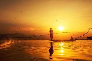 tirar red de pesca durante el atardecer foto