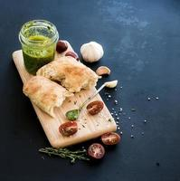 Pesto sauce in jar, ciabatta bread, cherry-tometoes, thyme and