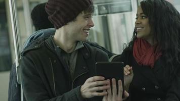 pareja joven en una cita usar una tableta en un tren
