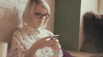 glückliche junge schöne Frau, die Kaffee im Café trinkt und SMS auf ihrem Smartphone schreibt