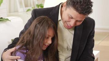 hija se sienta en el regazo de su padre con una tableta digital