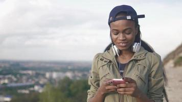 Close-up portrait of pretty hipster african american girl listening music outdoor. Blurred cityscape background