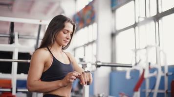 relógio inteligente mostrando a frequência cardíaca de uma mulher se exercitando na academia