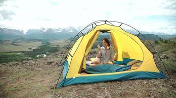 eine Frau am Telefon in ihrem Zelt und Schlafsack