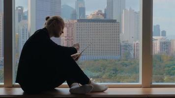 jovem sentada no parapeito da janela, usando o tablet e olhando pela janela. hong kong, china video