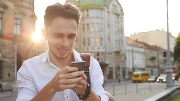 homme séduisant dans la vingtaine, tapant un message sur son smartphone dans un centre-ville au coucher du soleil. video
