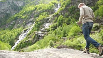 Randonneur homme photographiant la vallée au-dessus