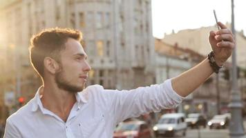 Handsome caucasian male in his 20s doing selfie outdoors in middle of european city center. Guy using frontal camera on his smartphone video