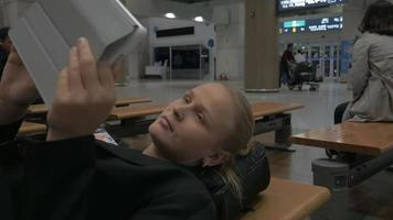 Mujer con almohadilla acostada en el banco en la terminal del aeropuerto