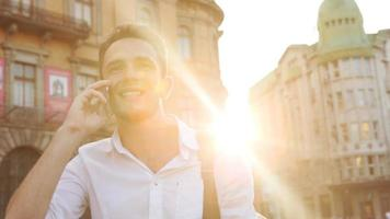 Young male smiling while having talk over cellphone in lense flares. Attractive guy actively doing smile.