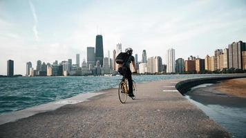 ciclista cavalga à beira-mar com arranha-céus ao fundo