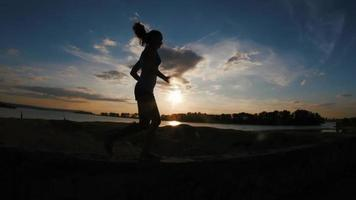 Running young woman in park at sunset, slow-motion, hands in a fist, silhouette video